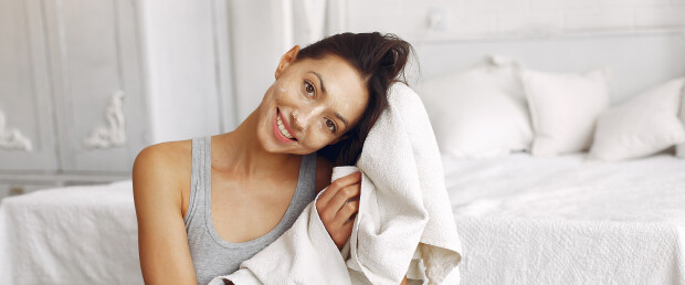 Girl in a studio. Lady in a white towel. Woman sitting near bed.
